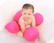 baby sitting in pink Papillon bath seat